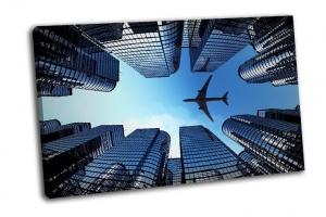 Самолет летящий над зданиями